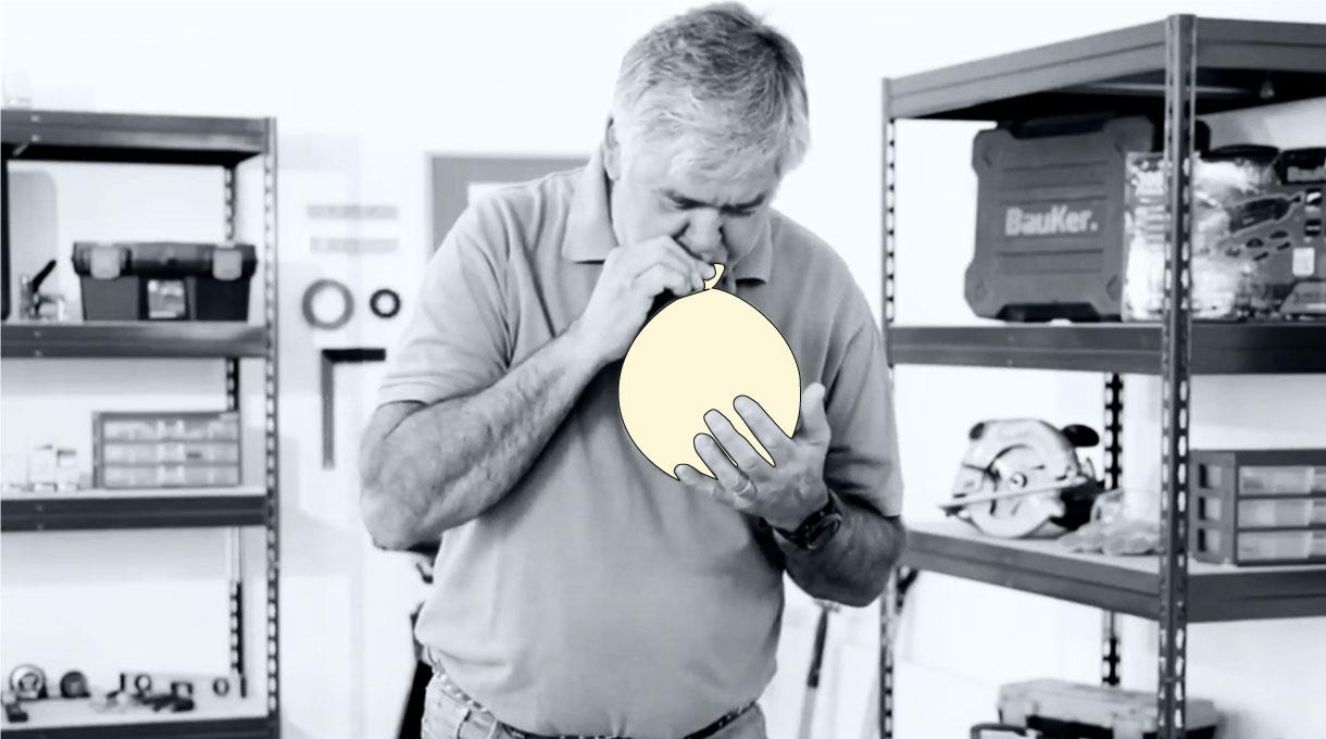Hombre inflando globo para lámpara como decoración casera de halloween