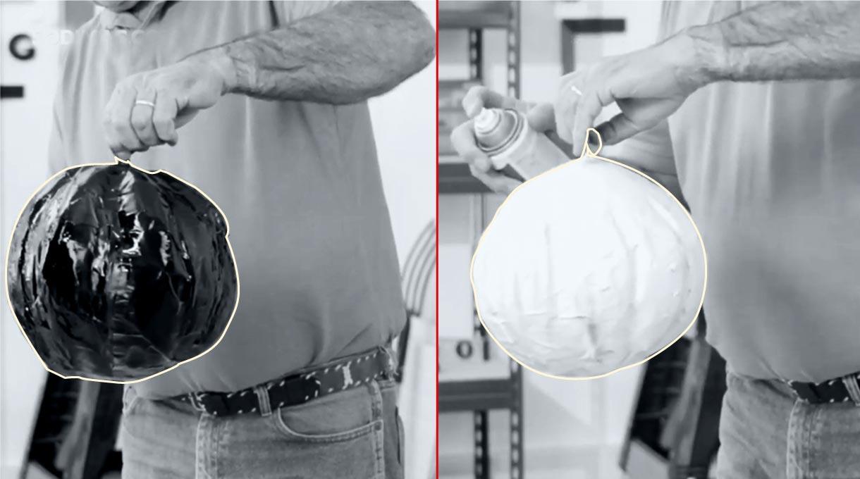 Hombre sosteniendo globo pintado de blanco y otro pintado de negro