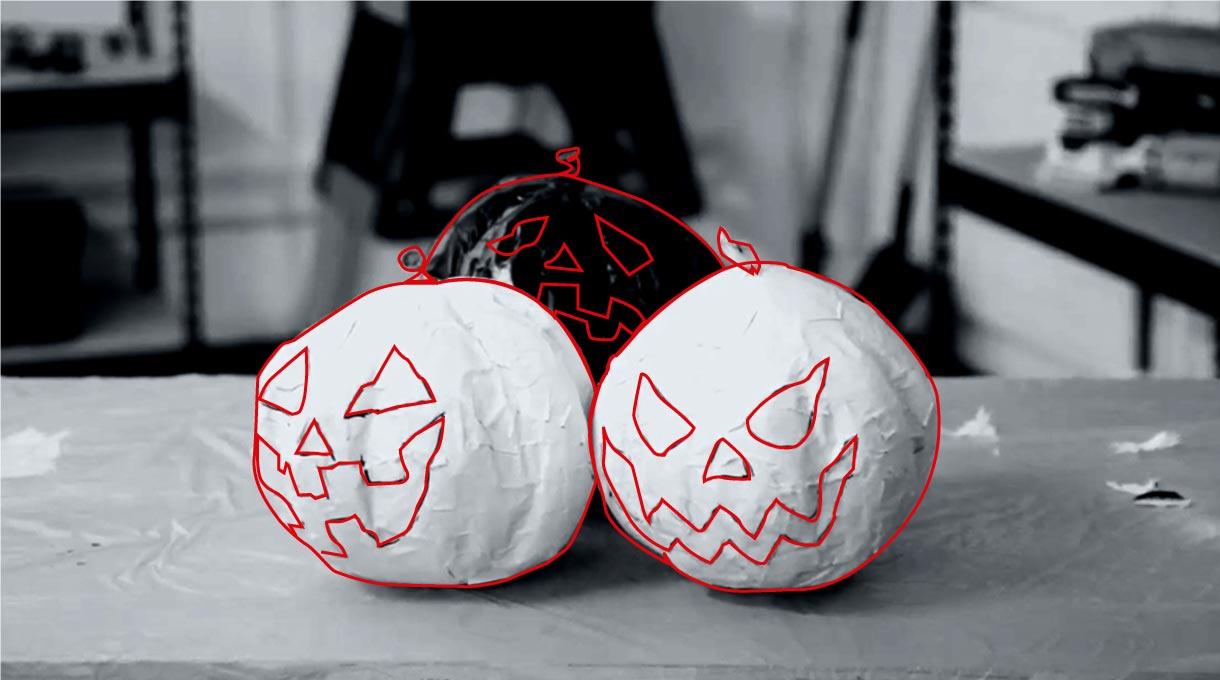 Dos calabazas blancas y una negra pintadas con caras maléficas