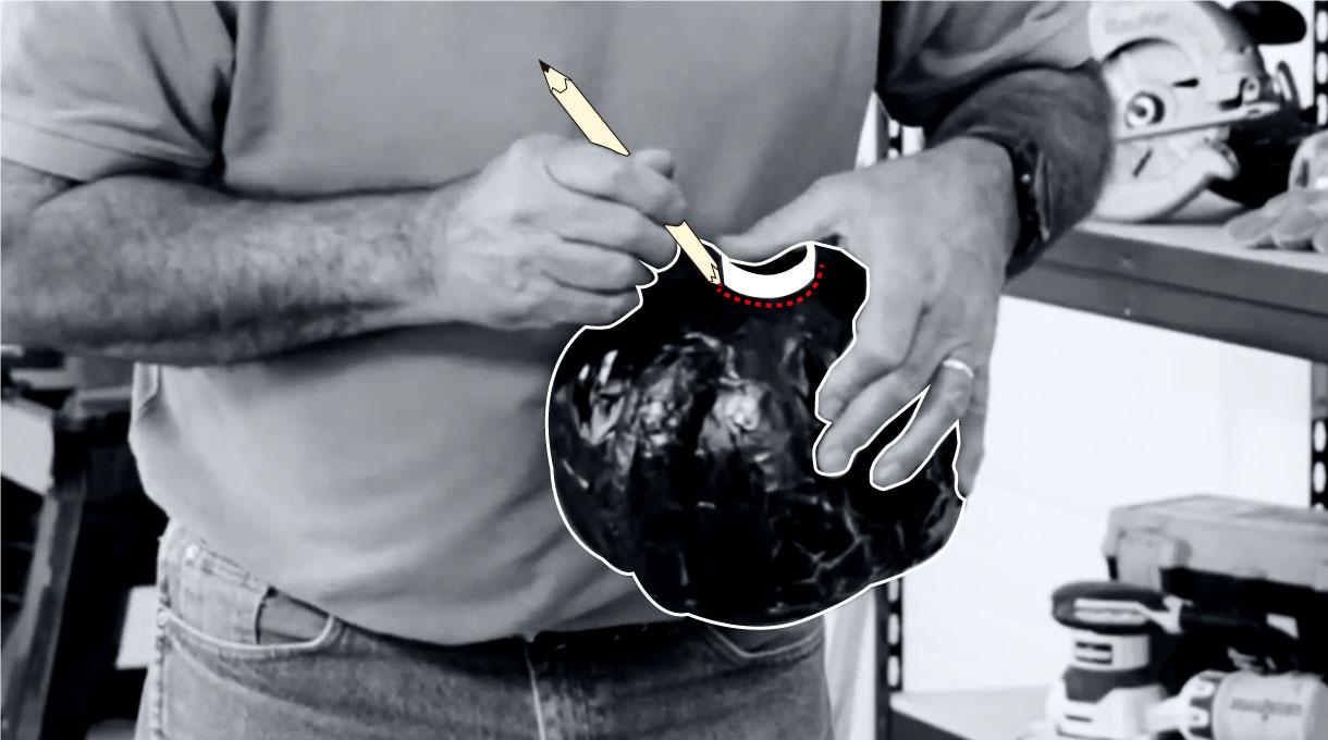 Hombre haciendo un agujero en calabaza negra de decoración casera de Halloween