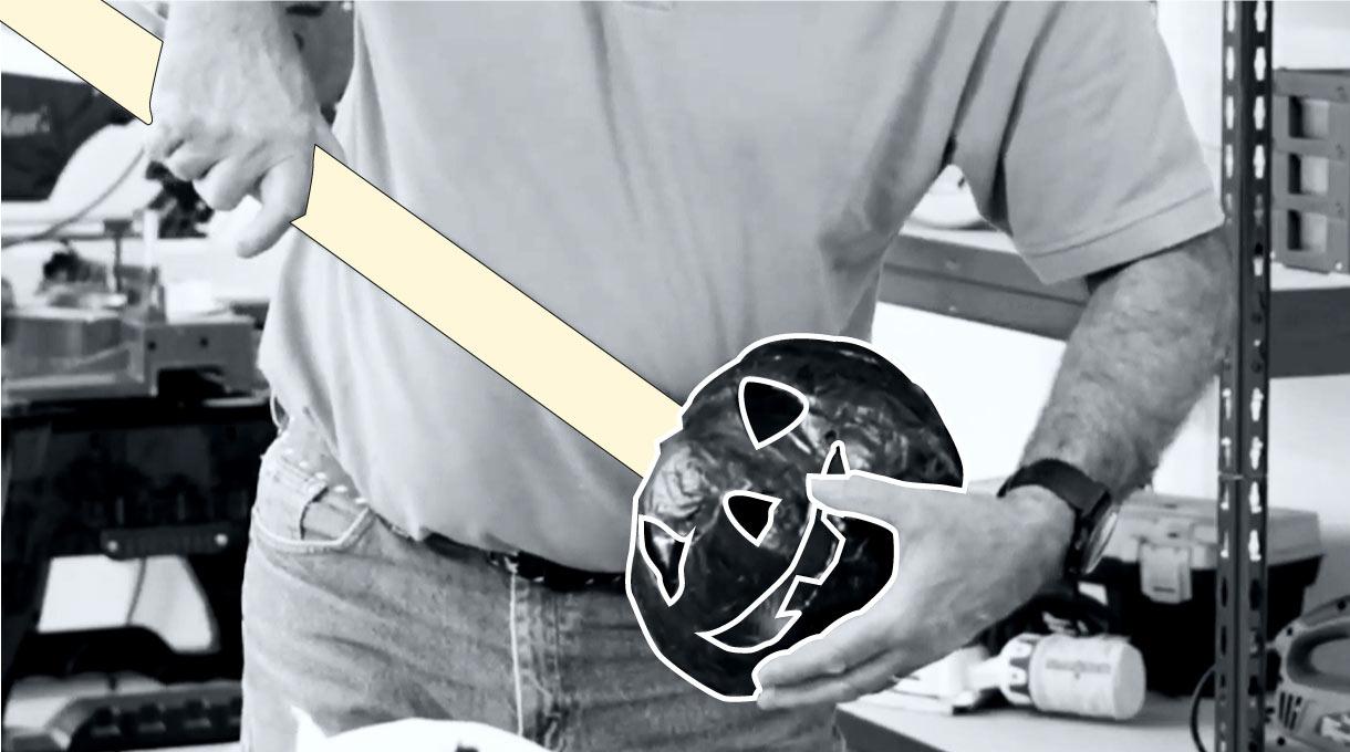 Hombre introduciendo tubo de PVC por agujero de la calabaza negra