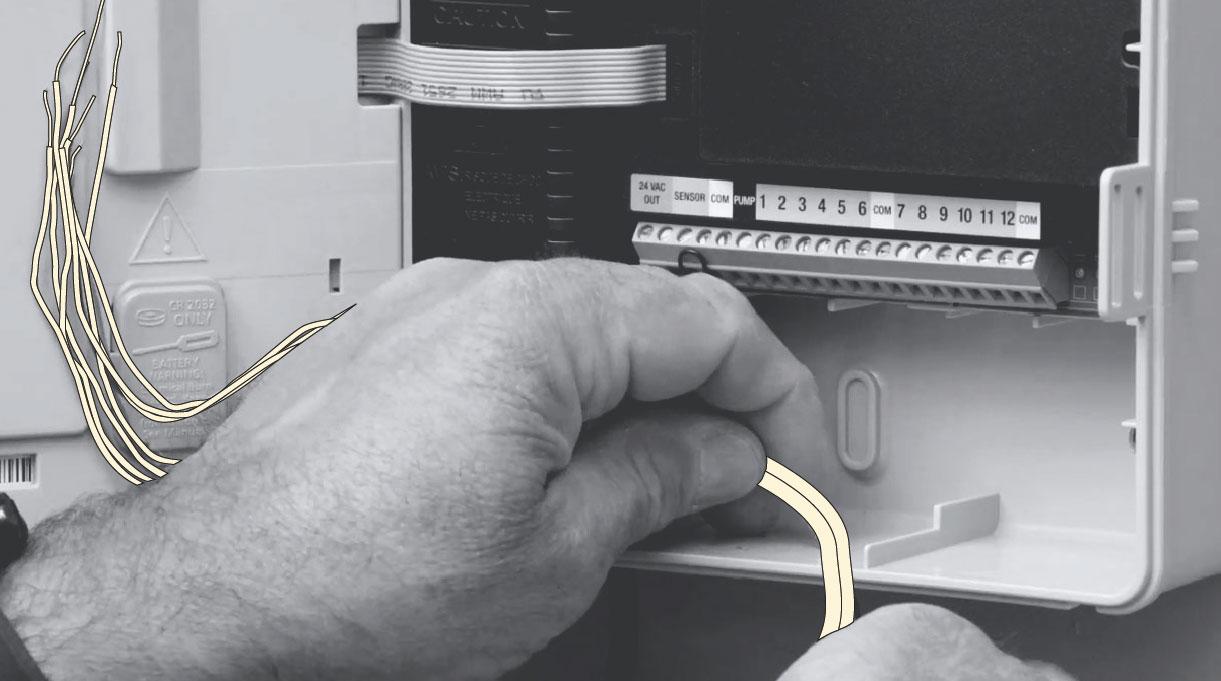 Persona manipulando los cables del programador de riego automático