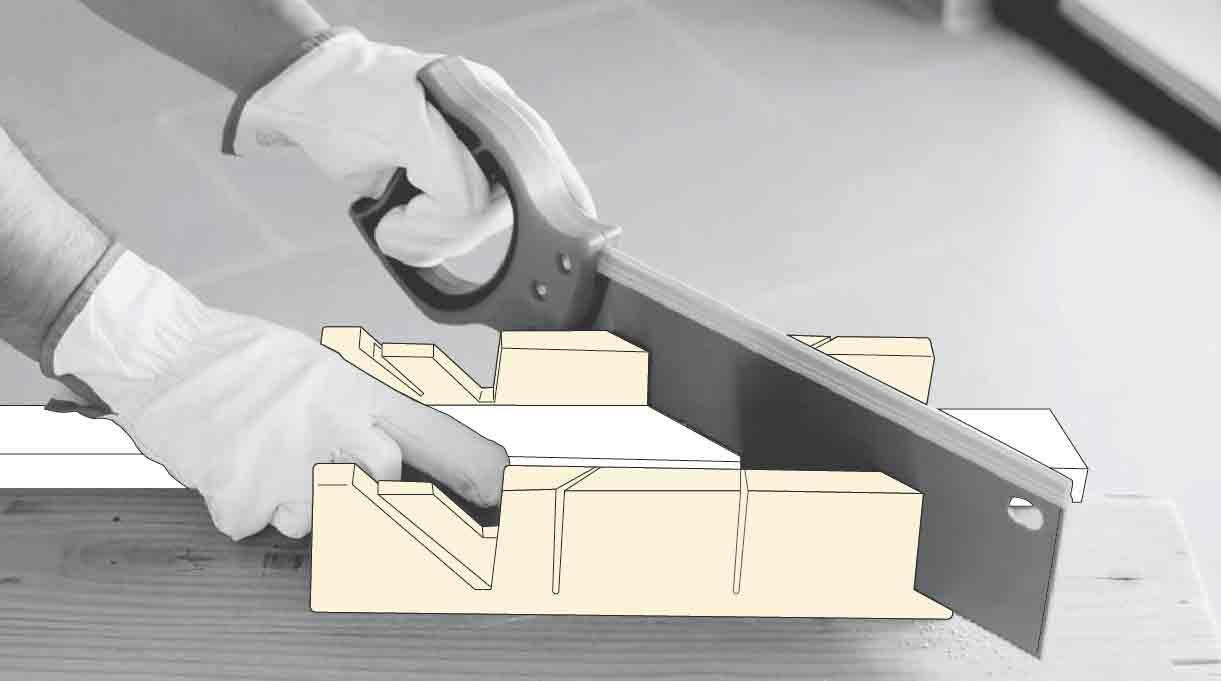 manos con serrucho cortando listón con la caja de ingletes