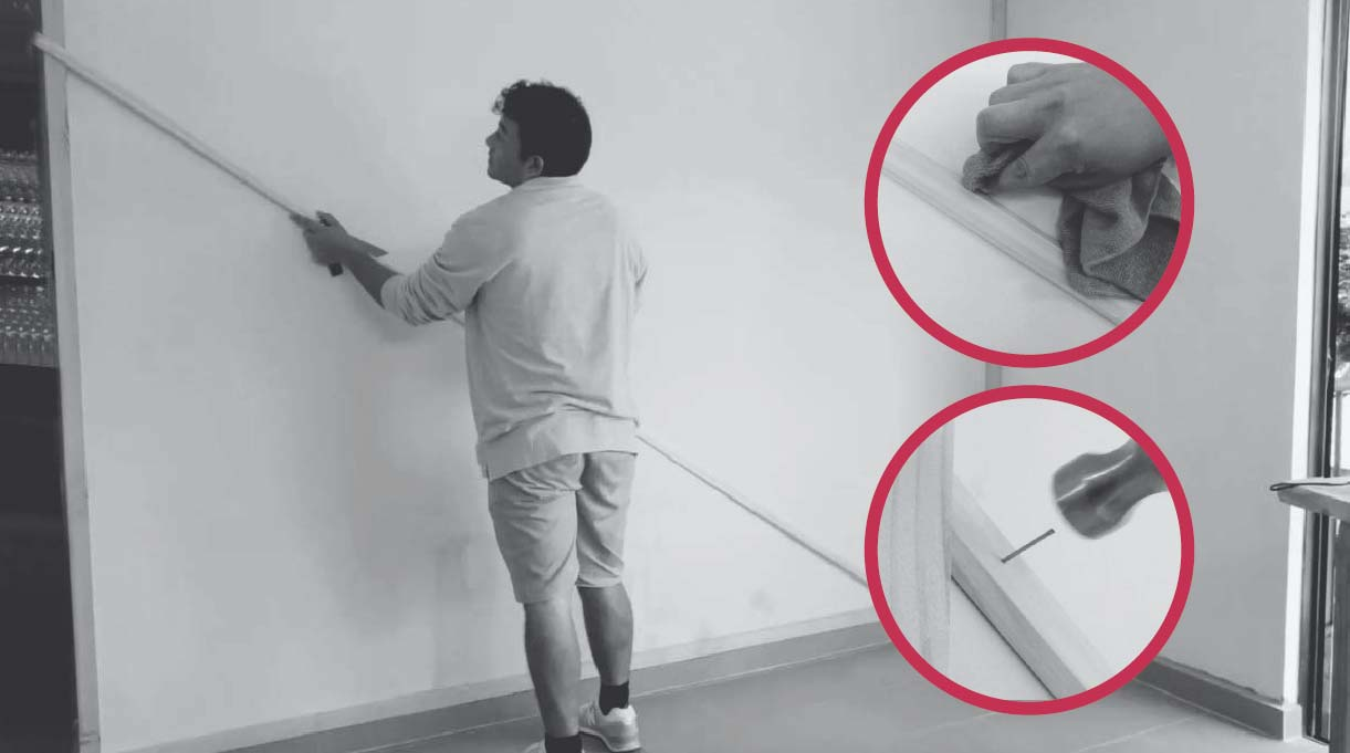 hombre pegando la primera moldura en el muro