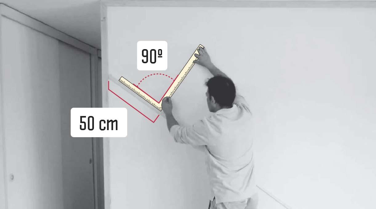 hombre midiendo para instalar la segunda moldura en el muro