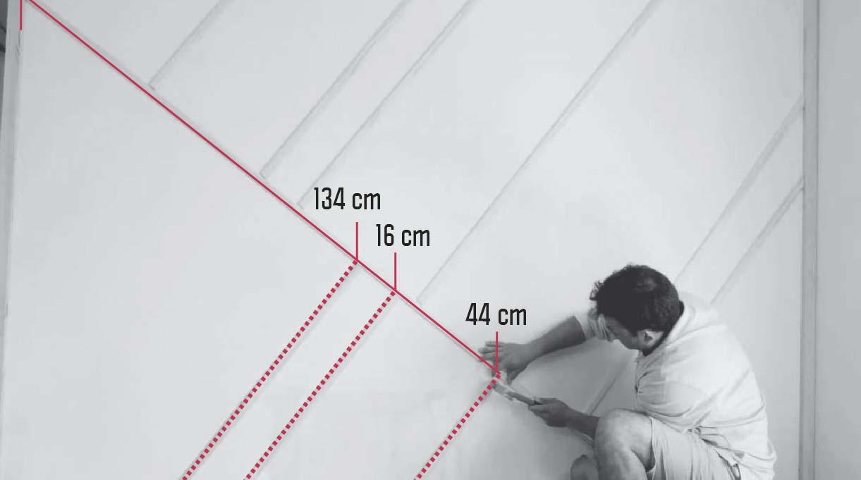 hombre marcando las medidas en el muro donde van las molduras inferiores