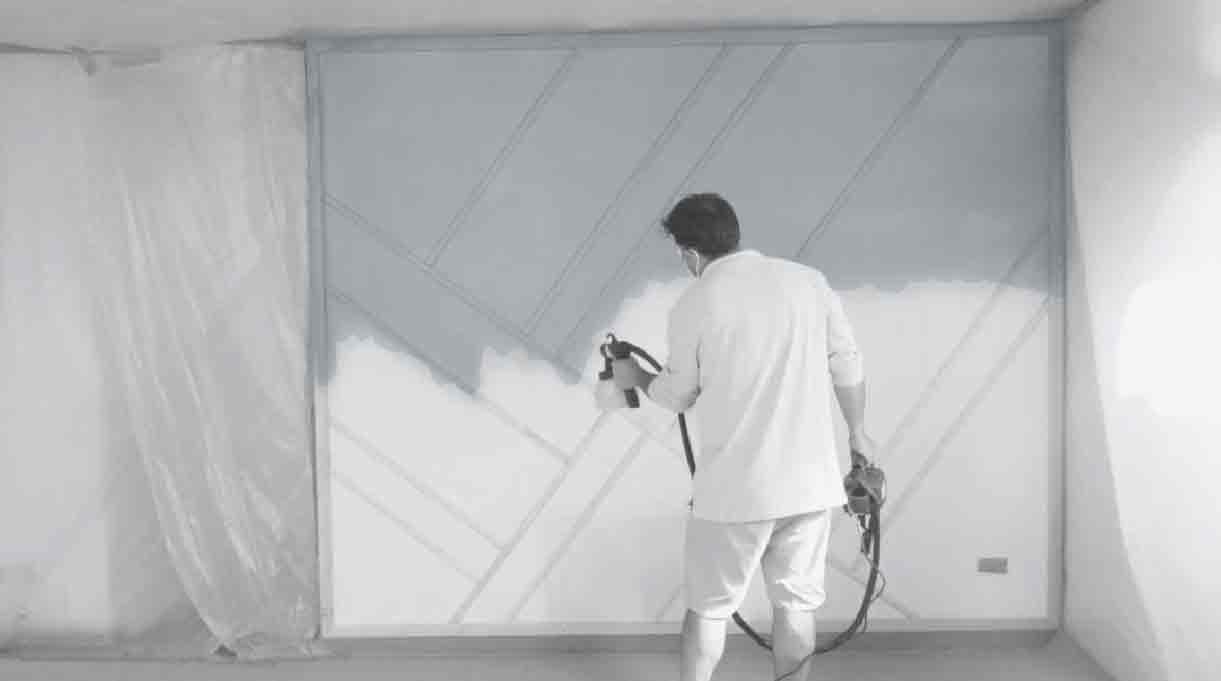 hombre pintando el muro con pistola pulverizadora