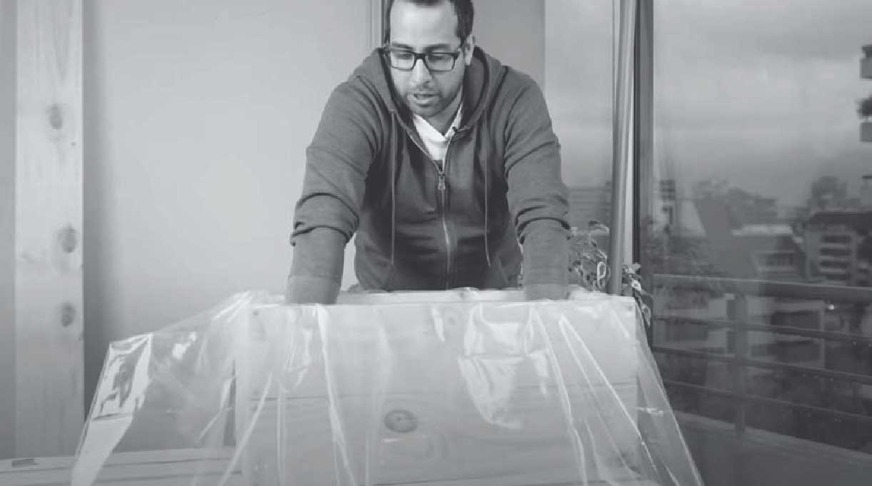 En la imagen aparece un hombre cubriendo el interior del macetero autorregante con plástico