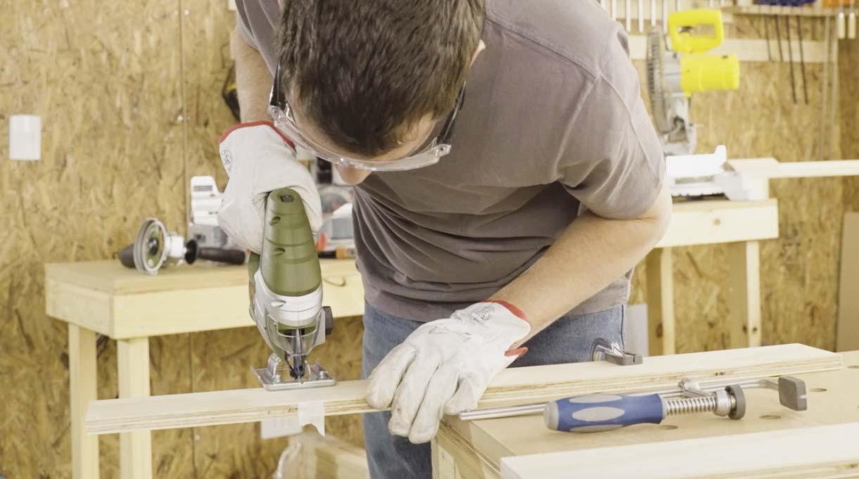 hombre cortando con la sierra caladora trozo de madera usando lentes y guantes de seguridad