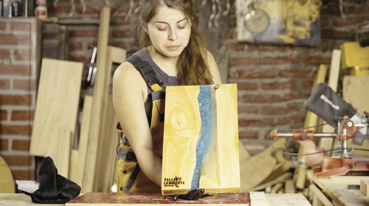 Mujer mostrando la tabla de picar con resina terminada