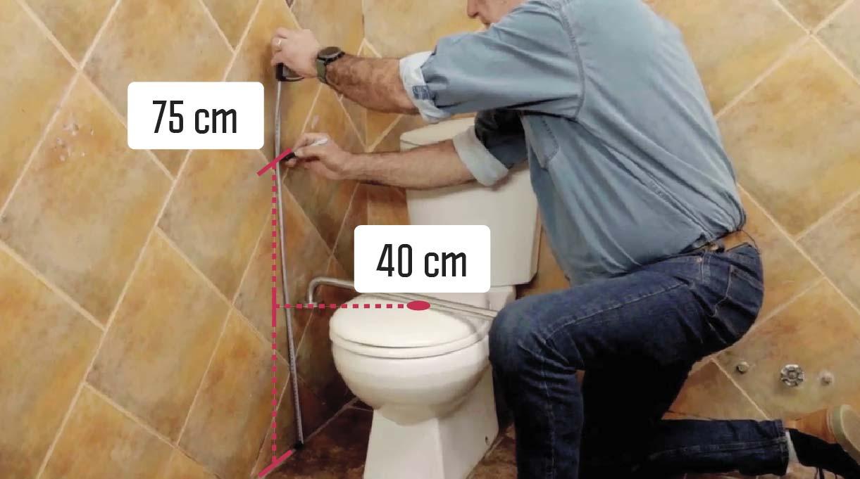 Alejandro Tardel midiendo para instalar las barras de seguridad a 75 cm desde el suelo y las barras para ayudar en el inodoro a 40 cm del eje del WC