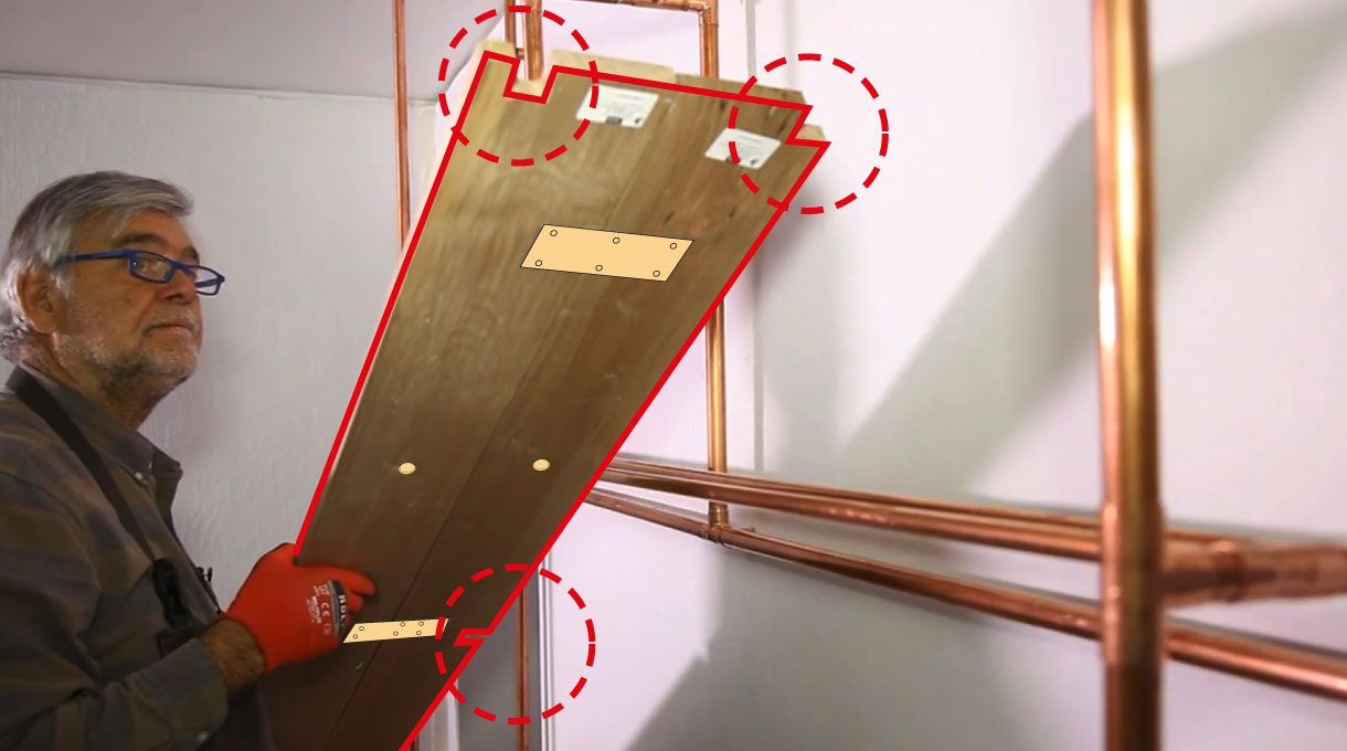 Tardel sujetando la tabla de roble del estante de cobre, que tiene los calados de 2 x 2 cm