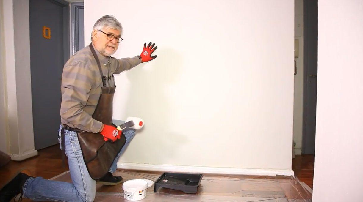 Tardel arrodillado en el piso, sosteniendo un rodillo para pintar en una mano y la otra apoyada en un muro blanco