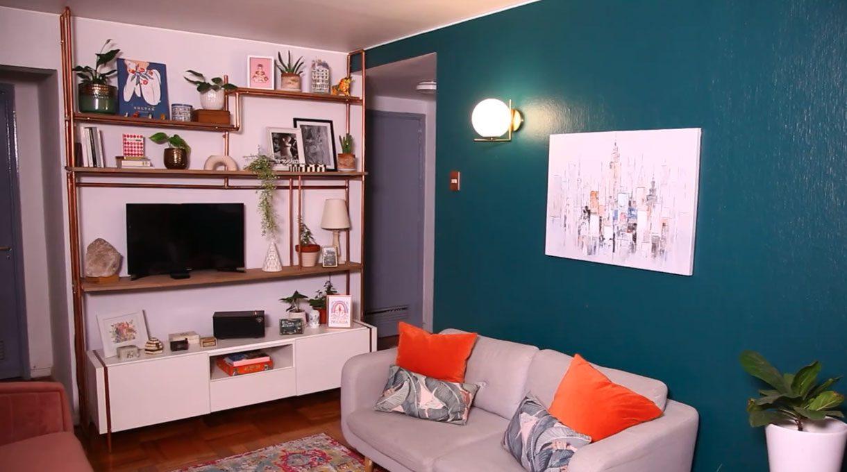 living con el estante de cobre terminado, con un televisor en una repisa y en las otras, objetos decorativos. También hay un sillón de dos cuerpos con cojines naranjos, y un cuadro en la pared verde que fue pintada para el proyecto. Al lado del curadro, un apliqué encendido.