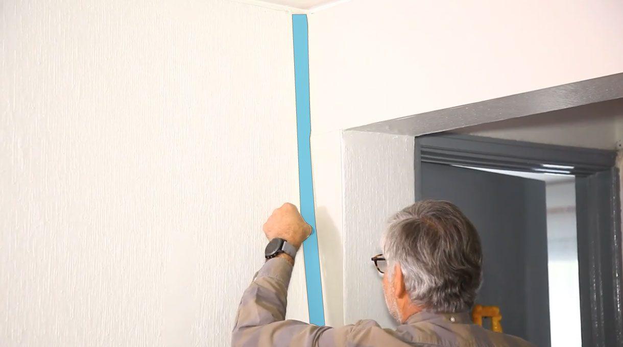 Alejandro Tardel colocando cinta de enmascarar antes de pintar