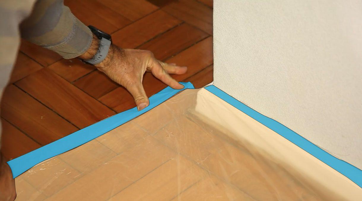 Tardel colocando cinta para enmascarar en el piso para que sujete un plástico protector para este